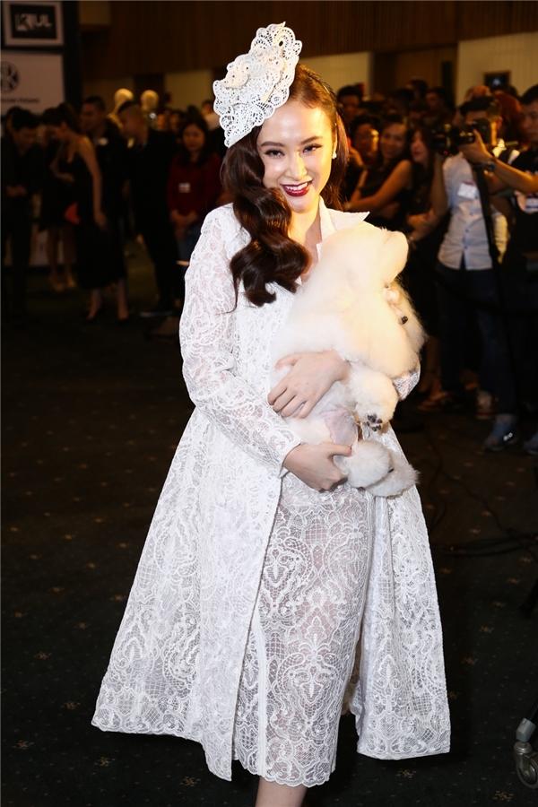 Với chú cún trên tay, Angela Phương Trinh thu hút mọi ống kính khi xuất hiện trên thảm đỏ show diễn cá nhân thứ hai của Chung Thanh Phong. Bộ cánh này cũng nhận nhiều ý kiến trái chiều khi khiến Angela Phương Trinh trông quá cầu kì, nặng nề.