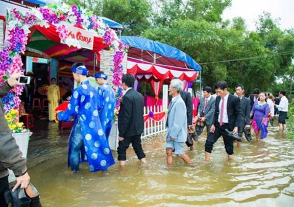 Họ hàng, khách khứa đều không ngại ngần xắn quần lội nước đi đón dâu.(Ảnh: Anh Đoàn)