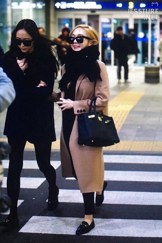 Krystal do mặc không đủ ấm nên phải ghì hai cổ áo để giữ ấm phần cổ.
