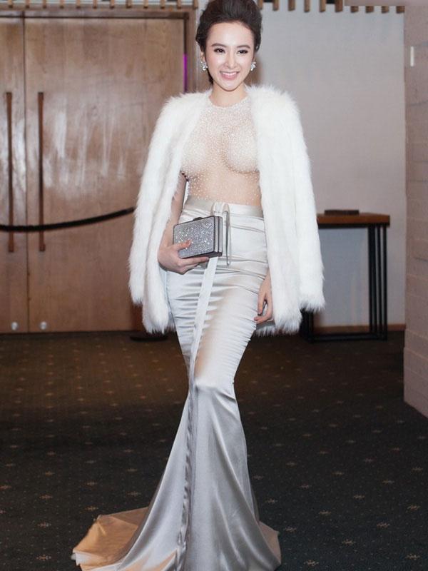 Angela Phương Trinh che phủ độ mỏng của phần thân váy nhờ áo lông có độ dài vừa phải. Màu trắng hòa quyện với tông xám bạc của trang phục một cách hoàn hảo.