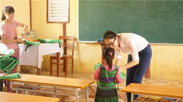 Diệu Ngọc trao cặp sách cho học sinh tiểu học.