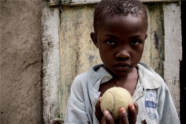 Trong một gia đình Haiti có thu nhập hơn 880.000 đồng/người lớn, cậu bé có được một trái bóng quần vợt để chơi.