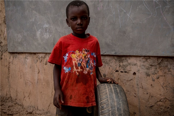 Trong một gia đình Burkina Faso khác với thu nhập hơn 1,2 triệu/người lớn, cậu bé có được chiếc lốp xe vứt đi làm đồ chơi.