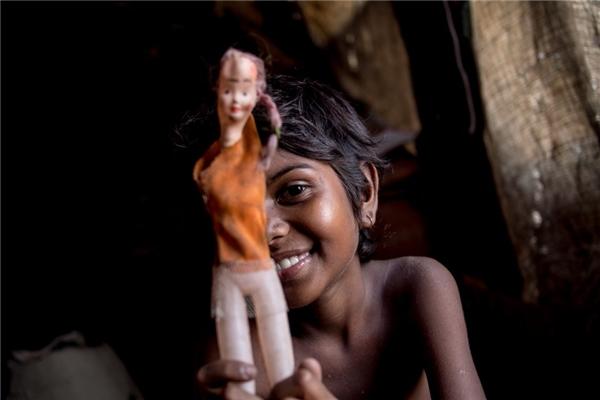Trong khi đó, một gia đình khác ở cùng quốc gia với thu nhập hơn 1,8 triệu đồng/người lớn, bé gái cười rất tươi khi cầm trong tay con búp bê nhựa bị hỏng của mình.