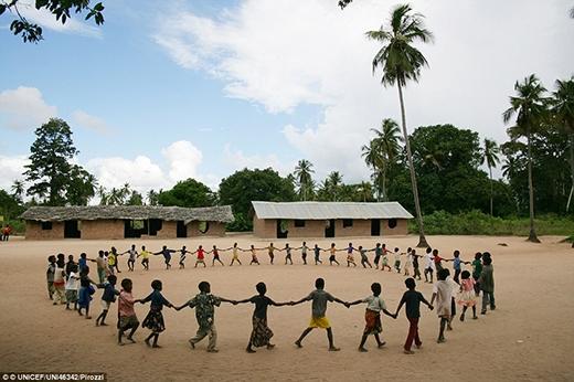Trong bức ảnh là những đứa trẻ nắm tay. chơi đùa với nhau thành hình vòng tròn, trong giờ ra chơi tại trường tiểu học Mulemba ở Maganja da Costa - một trong những quận nghèo nàn nhất của thị trấn Zambezia.