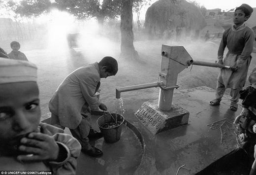 Hai đứa trẻ đi lấy nước tại máy lấy nước bằng tay ở vùng ngoại ô thị trấn Laghman.