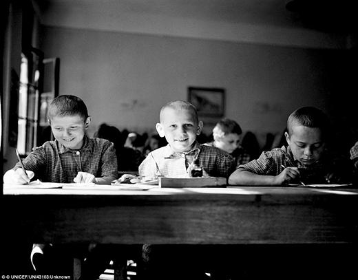 Ba bé traimặc bộ quần áo được quyền góp bởi Hội chữ thập đỏ Hà Lan đang ngồi học tại một ngôi trường thuộc thành phốKarlovac, phía tây bắc Croatia.