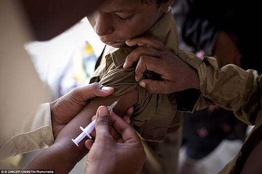 Một nhân viên y tế đang tiêm phòng cho một đứa trẻ tại trại dành cho những người chịu thiên tai lụ lụt tại Sukkur, thành phố thuộc thị trấn Sindh - nơi tổ chức Unicef và các tổ chức khác đang cung cấp dịch vụ tiêm ngừa uốn ván và vệ sinh giúp ngăn ngừa bệnh dịch lây lan.