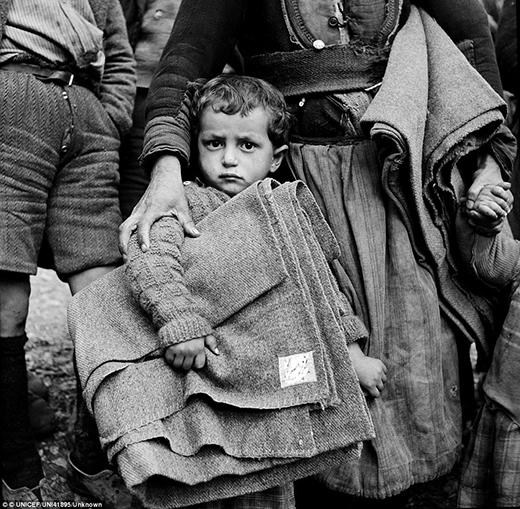 Một đứa trẻ ôm chiếc chăn viện trợ của Unicef và vịn vào váy của một người phụ nữ với một tay ôm vai bé ấy, một tay nắm tay đứa trẻ khác tại Circa năm 1950, phía tây bắc thị trấn Castoria.