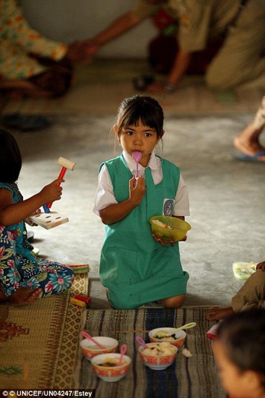 Và một bé gái đang ăn thức ăn tại trung tâm sức khỏe cộng đồng ở quận Klaten, thị trấn Central Java.
