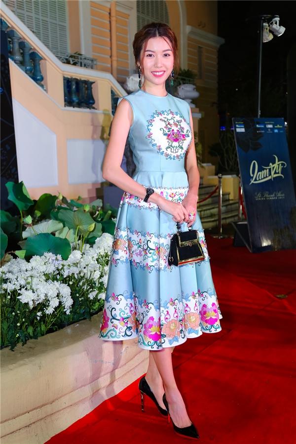 Á hậu Thúy Vân diện váy xòe đơn giản với hàng loạt họa tiết hoa lá, mang đậm dấu ấn phong cách của Lê Thanh Hòa.