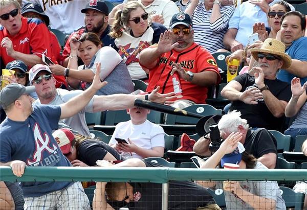 Nhiếp ảnh gia Christopher Horner chụp lại chính xác khoảnh khắc một người bố giơ tay ra đỡ cây gậy bóng chày bay thẳng vào mặt cậu con trai 8 tuổi đang ngồi chơi điện thoại say sưa trên khán đài một trận đấu bóng chày. Ngay sau trận đấu, người bố có phản xạ nhanh như chớp này được tuyên dương là người hùng.