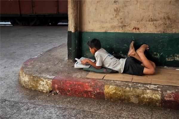 Một cậu bé ở Serbia nằm dài trên vỉa hè và chăm chú vào cuốn sách nhỏ.