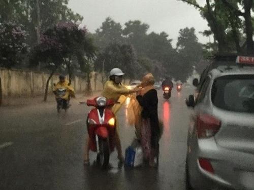 Bức ảnh cô gái đứng giữa trời mưa bão, mặc áo mưa cho bà cụ nghèo khiến nhiều người ấm lòng. Dù trong hoàn cảnh khắc nghiệt nhất, tình người vẫn lan tỏa và ấm áp đến lạ kì.
