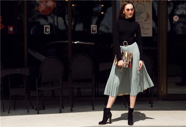 """Không cần quá rực rỡ hay """"kiệm vải"""" khi xuống phố nhưng Kim Duyên vẫn nổi bần bật bởi chiếc váy xếp ly xanh ghi mix-match cùng áo len đen cổ lọ. Tổng thể bộ trang phục thêm phần hoàn hảo hơn bởi đôi ankle boot và thắt lưng to bản."""