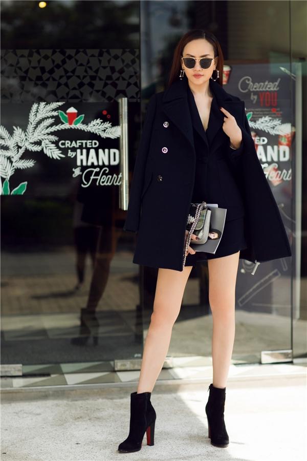 Kim Duyên chọn phong cách cổ điển sang trọng khi kết hợp áo vest đen cùng quần short ngắn. Trong những ngày tiết trời se lạnh thì chiếc áo khoác dạ sẽ là sự lựa chọn vô cùng thông minh. Người đẹp chọn đôi ankel boot giúp tăng thêm nét cá tính.