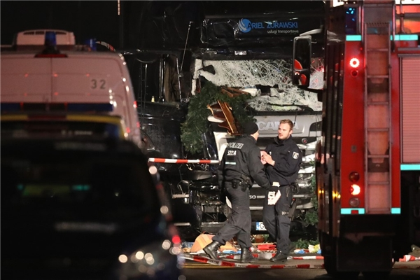 Cảnh sát và các nhân viên cứu hộ đứng cạnh chiếc xe tải thực hiện vụ tấn công vào phiên chợ Giáng sinh.