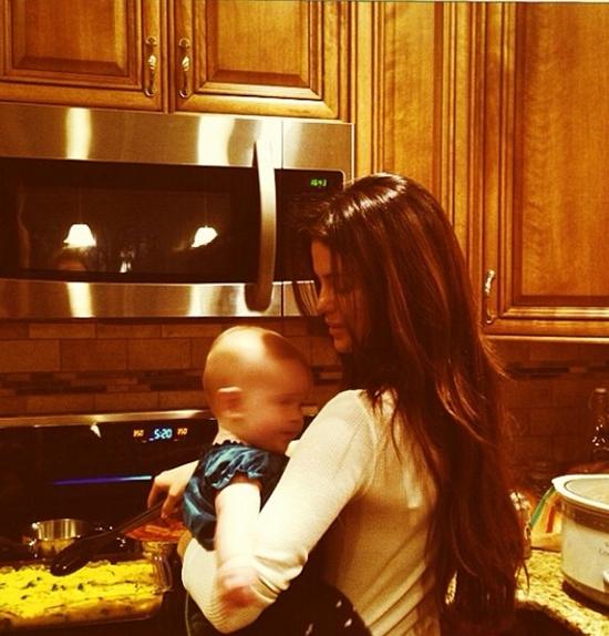 Selena mộttay bế cô em gáiGracie6 tháng tuổi vừa một tay chuẩn bị bữa ăn trên bếp.