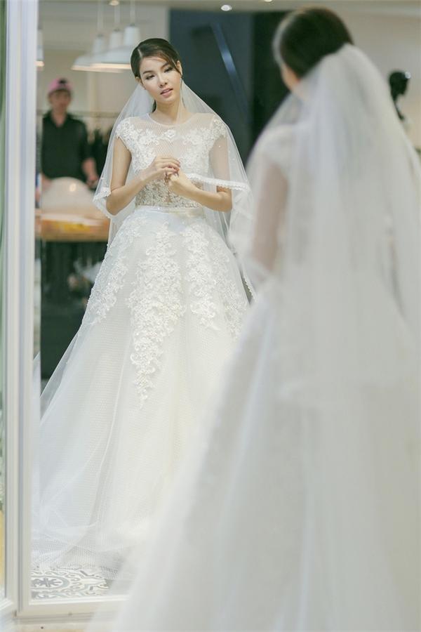 Trong tiệc cưới ở quê nhà hay tại TP.HCM để chiêu đãi bạn bè, Kỳ Hân luôn chọn diện váy cưới màu trắng với phom xòe rộng để che đi bụng bầu những tháng đầu tiên. Thiết kế cũng không quá cầu kì mà được tập trung khai thác ở các chi tiết ren đính kết.