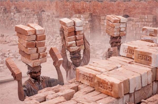 Các công nhân chưa qua đào tạo ở Trung Á mỗi ngày phải khiêng gạch bằng đầu như thế này, trong một môi trường khói bụi mịt mờ.