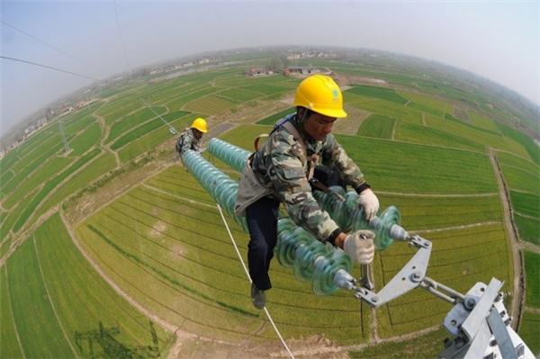 Đây là cảnh các công nhân đang leo lên cột điện cao thế ở Trung Quốc để bảo trì và sửa chữa.