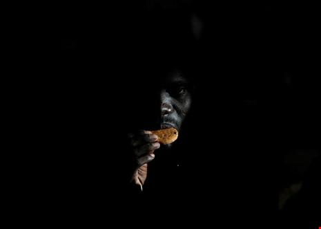 Một người di cư đang ăn một cái bánh được viện trợtại bờ biển của Libya. (Ảnh: internet)