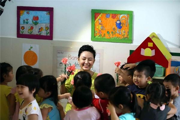 Nga nở nụ cười rạng rỡ trong vòng vay của các học trò nhỏ.(Ảnh: Thanhnien.vn)