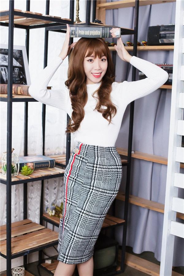 Luk Vân chọn áo len trắng kết hợp với chân váy ôm sát sọc caro chất liệu nỉ rất nữ tính.