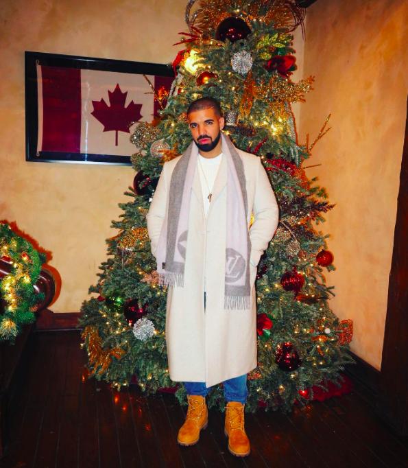 Drake chụp ảnh bên cây thông Noel và quốc kỳ Canada - quê hương của anh.