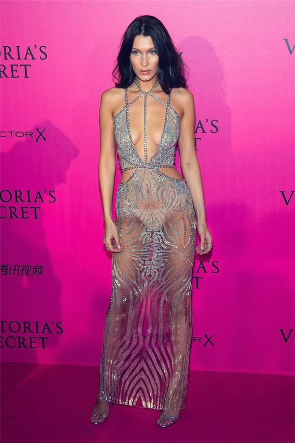 """Tuy là lính mới nhưng người mẫu Bella Hadid đã tỏ ra vô cùng kinh nghiệm trong khoản mặc đồ hở. Bằng chứng là cô nàng đã """"chặt chém"""" hết thảy các đàn chị trong bữa tiệc hậu Victoria's Secret Fashion Show 2016 với chiếc đầm ánh bạc xuyên thấu phô bày tới hơn 90% cơ thể."""