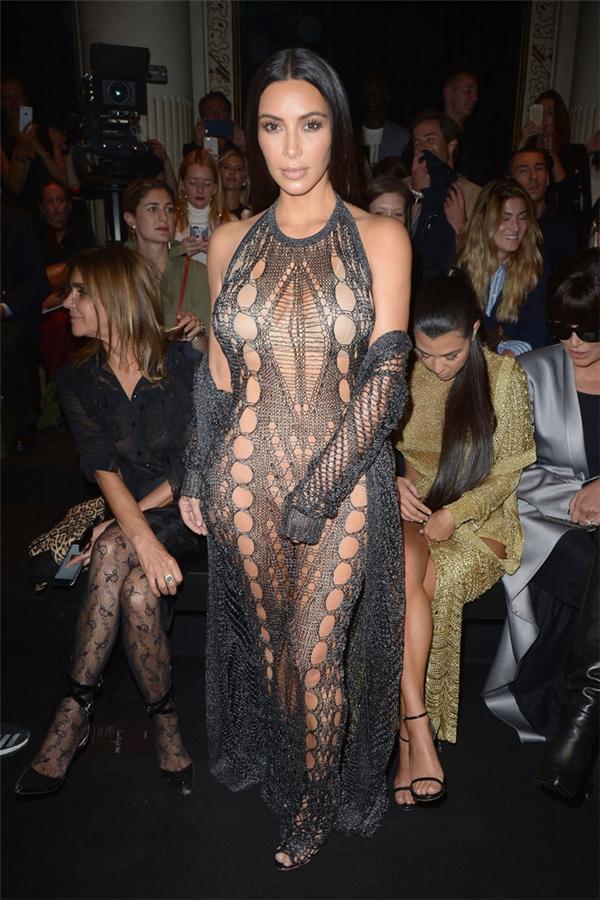 """Nếu nói đến nữ hoàng của những bộ đầm xuyên nấu, """"mặc như không mặc"""" thì phải nói đến Kim Kardashian. Cô nàng đã diện bộ đầm đan mà Olivier Rousteing thực hiện riêng này đến Tuần lễ Thời trang Balmain Paris. Mặc dù Kim đã diện nội y màu nude bên trong nhưng có vẻ cô nàng bỗng có chút ngại ngần khi lấy tay che vùng nhạy cảm của mình lại khi thấy ánh đèn flash hướng về cô."""