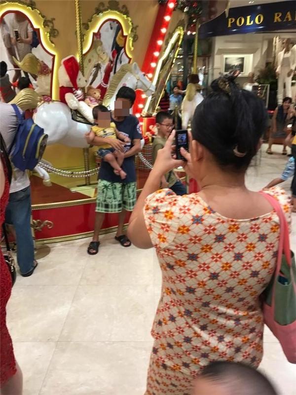 Chị vợ đứng chụp hình cho chồng và cô con gái nhỏ.(Ảnh: Internet)