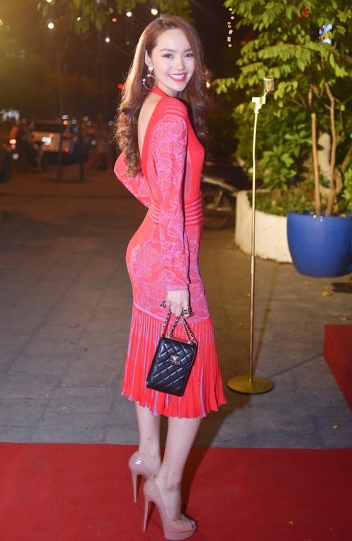 Tham dự đám cưới của Trấn Thành, Minh Hằng chọn diện bộ váy hàng hiệu với sắc đỏ hồng ngọt ngào, duyên dáng. Thiết kế với loạt chi tiết màu tím tạo độ phản quang những mảng sáng, tối cho trang phục trông rất thú vị, bắt mắt.