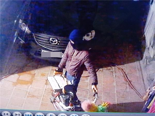 Tên trộm di chuyển đồ đạc trong sân để lấy khoảng trống dắt xe máy ra ngoài.