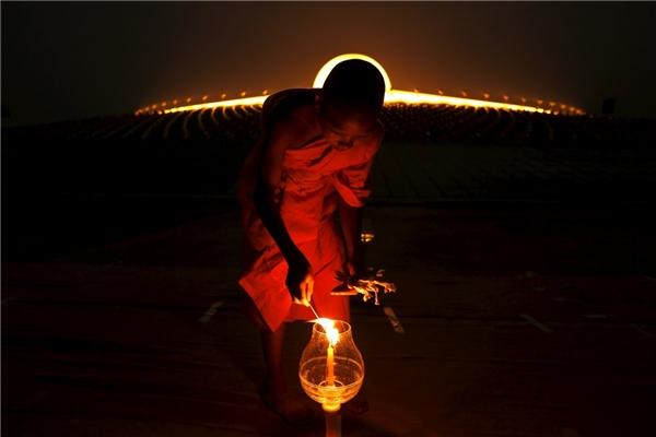 Một vị sư thắp nến ở chùa Wat Phra Dhammakaya trong buổi lễ Makha Bucha ở tỉnh Pathum Thani, bắc Bangkok vào ngày 22/2.