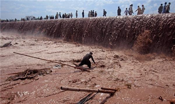 Một người chủ cố gắng cứu những món hàng của mình trong khi người dân đang đi qua cây cầu ngập nước lũ ở vùng ngoại ô Peshawar, Pakistan, vào ngày 4/4.