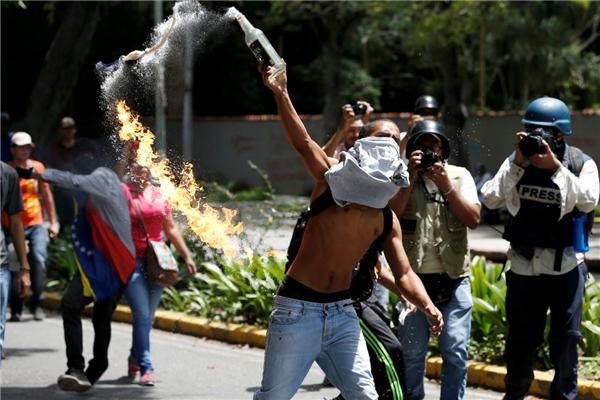 Một người biểu tình đổ chai cốc-tai Molotov trong một cuộc biểu tình của sinh viên đại học nhằm chống lại chính phủ Venezuela ở Caracas, Venezuela, vào ngày 9/6.