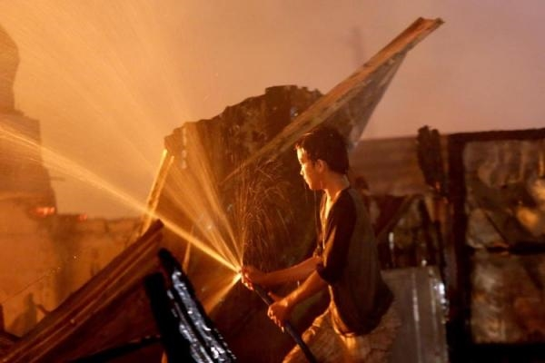Người đàn ông cố gắng phun nước để dập tắt đám cháy nhưng có vẻ bất lực. (Ảnh: Internet)