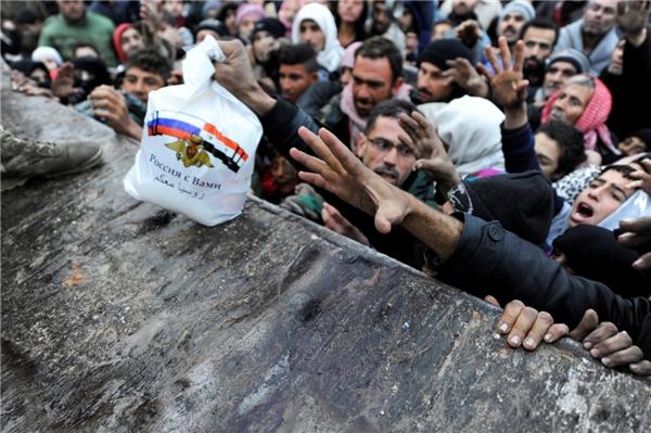 """Người Syria sơ tán đến phía đông Aleppo nhận lương thực viện trợ của Nga tại khu vực Jibreen do chính phủ kiểm soát vào ngày 30/11. Dòng chữ trên chiếc túi trong tiếng Ả Rập có nghĩa là: """"Nước Nga luôn bên bạn"""", cùng với hình ảnh quốc kì Syria đặt cạnh quốc kì Nga."""