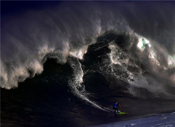 Một người lướt sóng cưỡi một con sóng lớn ở El Bocal trong một cuộc thi lướt sóng Vaca Gigante (Con bò lớn) ở Santander, phía bắc Tây Ban Nha, vào ngày 17/12.
