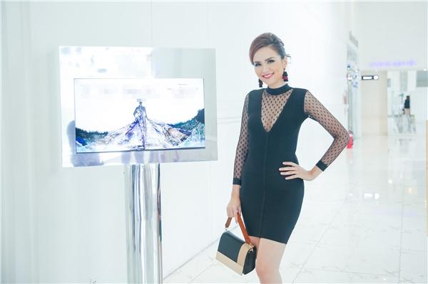 Hoa hậu Thế giới người Việt 2010 Diễm Hương dành thời gian đến chúc mừng nhà thiết kế Quỳnh Paris. Cô diện bộ váy cocktail ôm sát với sắc đen cá tính, mạnh mẽ kết hợp bodysuit bằng lưới mỏng manh bên trong.