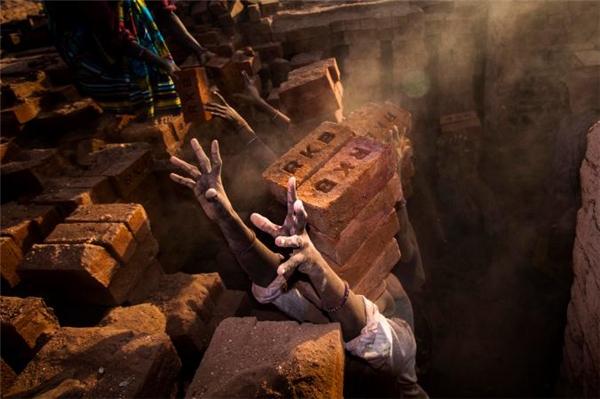 """Nhiếp ảnh gia Sanjay Ramani đã ghi lại cảnh tượng gây ám ảnh ở một sân gạch tại Ấn Độ: những người thợ cố gắng giữthăng bằng các khối gạch trên đầu vàchìa bàn tay lem luốc ra để xin thêm gạch. """"Ở đâychỉ có phụ nữ làm nhiệm vụ chuyển gạch từ nơi này sang nơi khác"""", anh còn cho biết."""