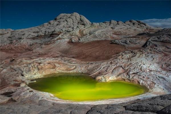 Ngắm bức ảnh chụp tại khu vực White Pocket, bắcParia Canyon (Arizona, Mỹ),hẳn ai cũng đều có cảm giác đang lạc vào một hành tinh khác với những dãy núi huyền ảo trên nền cát đỏ cùng hồ nước màu xanh lục. Hiện tượng này được lí giải là do có quá nhiều tảo sinh sôi khiến nước hồ trở nên đổi màu.