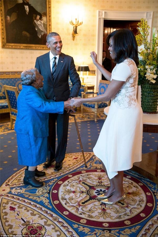 Tổng thống Barack Obama cười rạng rỡ nhìn Đệ nhất Phu nhân Michelle Obama khiêu vũ với cụ bà 106 tuổi trong Phòng Xanh, Nhà Trắng.