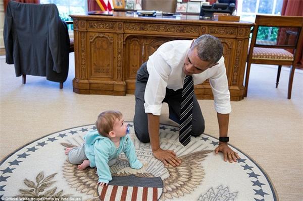 Tổng thống Obama quỳ trên nền đất, xắn tay áo cùng chơi đùa với bé gái của giám đốc truyền thông Jen Psaki.