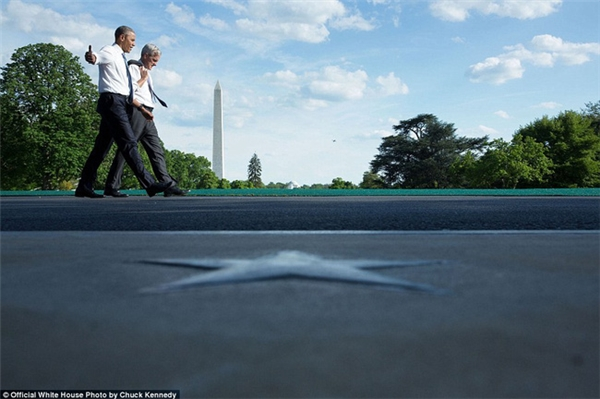 Ông Obama dạo bước trên đường South Law với Chánh văn phòng Denis McDonough, phía xa là đài tưởng niệm Washington.