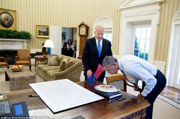 Ông Obama cúi người, phồng má dùng sức thổi nến trong ngày sinh nhật hôm 4/8/2016.