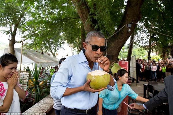 Tổng thống Obama đeo kính râm, uống nước dừa trên một quán ăn vỉa hè trong chuyến công tác tới Lào.