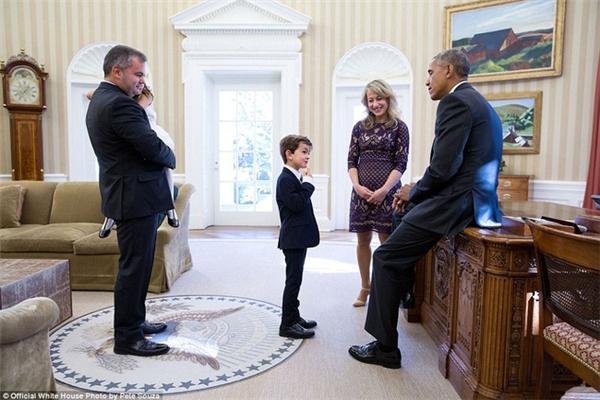"""Tổng thống Obama nghiêm túc lắng nghe Alex Myteberi – bé trai nổi tiếng với """"Thư gửi ông Obama"""" với nội dung xin được nhận nuôi cậu bé Syria Omran Daqneesh."""