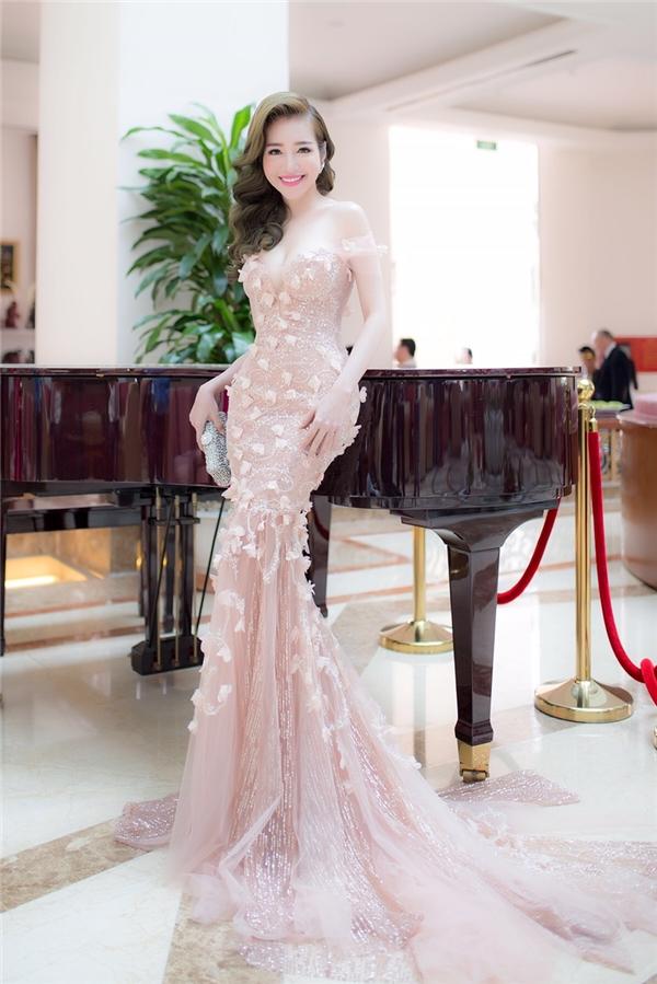 Elly Trầndiện trang phục dạ hội lộng lẫy với chất liệu ánh kim kết hợp hoạ tiết đính 3D đầy lãng mạn dự sự kiện ở TP.HCM. Bộ váy được thiết kế với phần ngựcxuyên thấuvà xẻ sâu vô cùng gợi cảm.